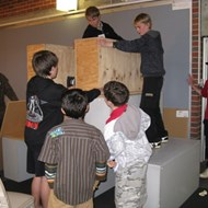 Boys building with large wooden boxes