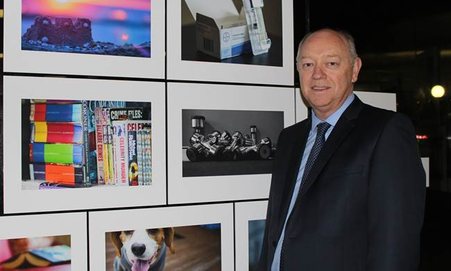 Commissioner Colin Pettit with some of the images by young people involved in the 2016 at Home Is Where The Heart Is exhibition.jpg