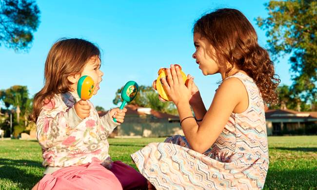 Photo Image - 2 young girls playing on grass.jpg